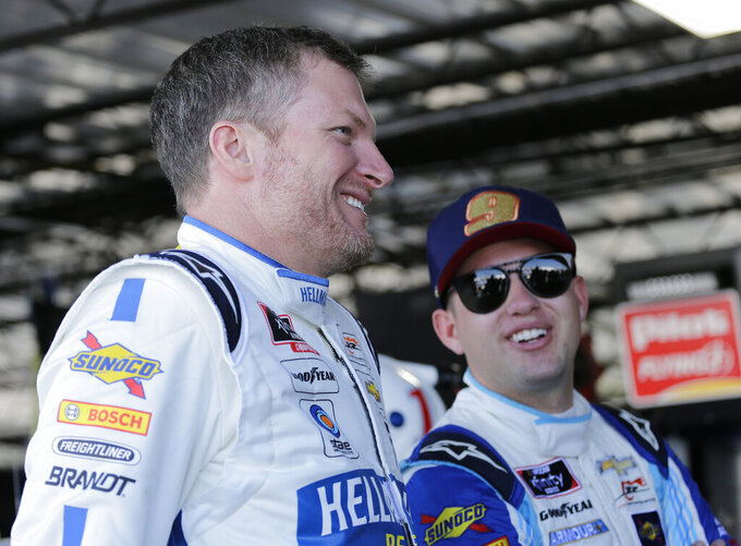 Dale Earnhardt Jr., left, talks with fellow driver Noah Gragson in the garage before practice for a NASCAR auto race on Friday, Aug. 30, 2019, in Darlington, S.C. Earnhardt is scheduled to run in the Xfinity race on Saturday. (AP Photo/Terry Renna)