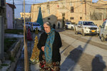 In this Jan. 18, 2019 photo, a woman walks in from of the Mart Shmony Orthodox Church in Bartella, Iraq. Two years after it was liberated from Islamic State militants, only a fraction of Christian residents have returned to Bartella. Many fear intimidation by the town's population of Shabak, a Shiite Muslim ethnic group who dominate the militias that now run Bartella. (AP Photo/Fay Abuelgasim)