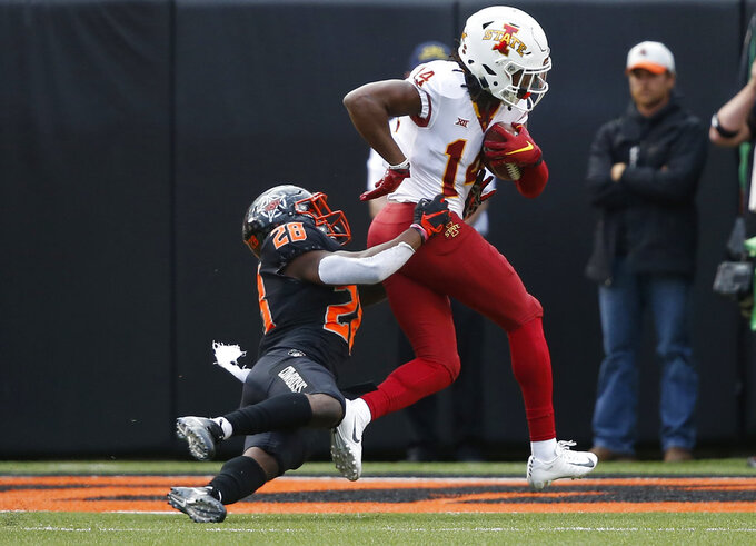 Iowa State wide receiver Tarique Milton (14) drags Oklahoma State safety Thabo Mwaniki (28) into the end zone as he scores in the second half of an NCAA college football game in Stillwater, Okla., Saturday, Oct. 6, 2018. (AP Photo/Sue Ogrocki)