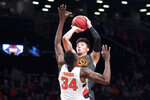 Oklahoma State guard Lindy Waters III shoots a 3-point goal over Syracuse forward Bourama Sidibe (34) during the first half of an NCAA college semi final basketball game in the NIT Season Tip-Off tournament, Wednesday, Nov. 27, 2019, in New York. (AP Photo/Mary Altaffer)