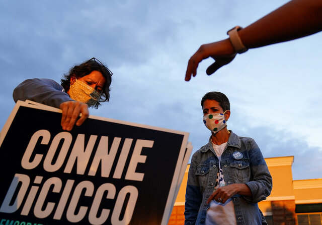 Georgia State Representative and Democratic candidate of District 44, Connie Di Cicco, center, looks on as her campaign manager, Katie Terry, left, hands out signs on Sunday, Oct. 11, 2020, in Marietta, Ga. Calling themselves sign ninjas, a group of people, including Di Cicco, routinely gather to trade and assemble campaign signs around their districts for local elections in Georgia and then venture out in the dark to install them along main thoroughfares. (AP Photo/Brynn Anderson)