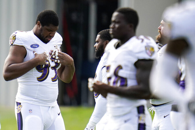Baltimore Ravens defensive end Calais Campbell adjusts his jersey before warming up during an NFL football camp practice, Monday, Aug. 17, 2020, in Owings Mills, Md. (AP Photo/Julio Cortez)