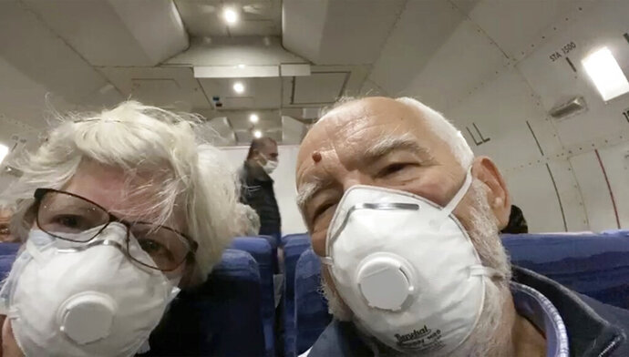 In this image from a video taken on Monday, Feb. 17, 2020, Paul Molesky, right, and Cheryl Molesky, who evacuated off the quarantined cruise ship the Diamond Princess, film selfie video aboard a Kalitta Air plane bound for the U.S., at Haneda airport in Tokyo.(Cheryl and Paul Molesky via AP)