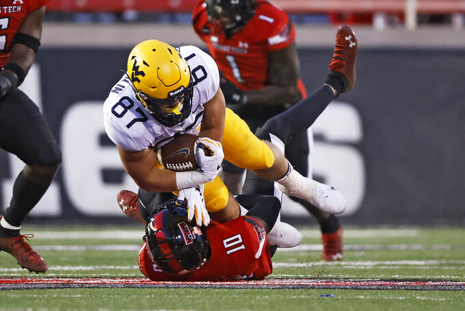 Texas Tech's Cam White (10) tackles West Virginia's Mike O'Laughlin (87) during the second half of an NCAA college football game on Saturday, Oct. 24, 2020, in Lubbock, Texas. (AP Photo/Brad Tollefson)