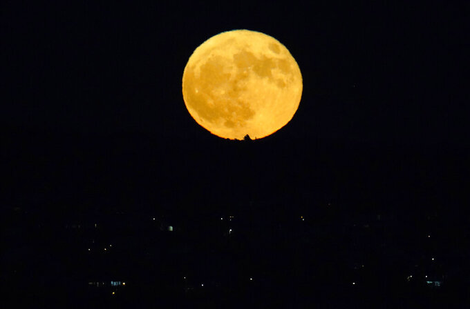 A rare Halloween blue moon rises in the second half of an NCAA college football game between Boise State and Air Force, Saturday Oct. 31 2020, at Air Force Academy, Colo. (AP Photo/David Zalubowski)