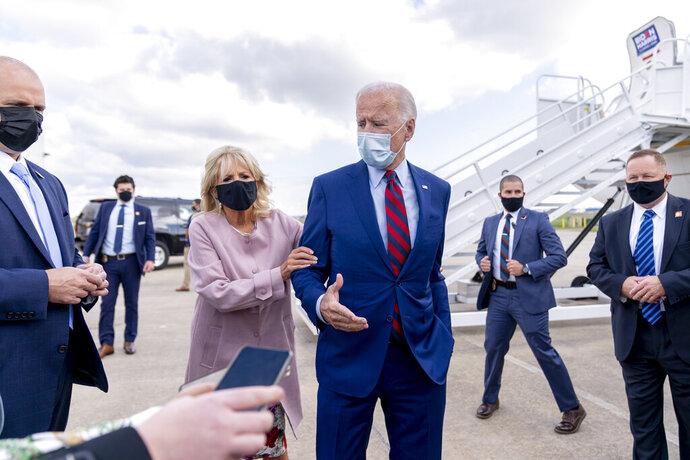 FILE - In this Oct. 5, 2020 file photo, Jill Biden moves her husband, Democratic presidential candidate former Vice President Joe Biden, back from members of the media as he speaks outside his campaign plane at New Castle Airport in New Castle, Del., to travel to Miami for campaign events. Protecting Joe stands out among Jill Biden's many roles over their 43-year marriage, as her husband's career moved him from the Senate to the presidential campaign trail and the White House as President Barack Obama's vice president. She's a wife, mother, grandmother and educator with a doctoral degree — as well as a noted prankster who will soon be putting her own stamp on what it means to be first lady. (AP Photo/Andrew Harnik, File)