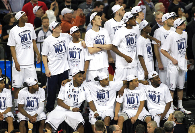 """FILE - In this April 4, 2011, file photo, Connecticut players watch the """"One Shining Moment"""" video after the men's NCAA Final Four college basketball championship game against Butler in Houston. Connecticut won 53-41. Nearly everyone involved in the men's college basketball tournament, it seems, cherishes a """"One Shining Moment"""" memory. (AP Photo/Mark Humphrey, File)"""