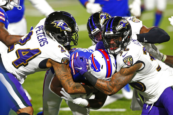 Baltimore Ravens' Marcus Peters (24) and Chuck Clark (36) tackle Buffalo Bills' Devin Singletary during the first half of an NFL divisional round football game Saturday, Jan. 16, 2021, in Orchard Park, N.Y. (AP Photo/John Munson)