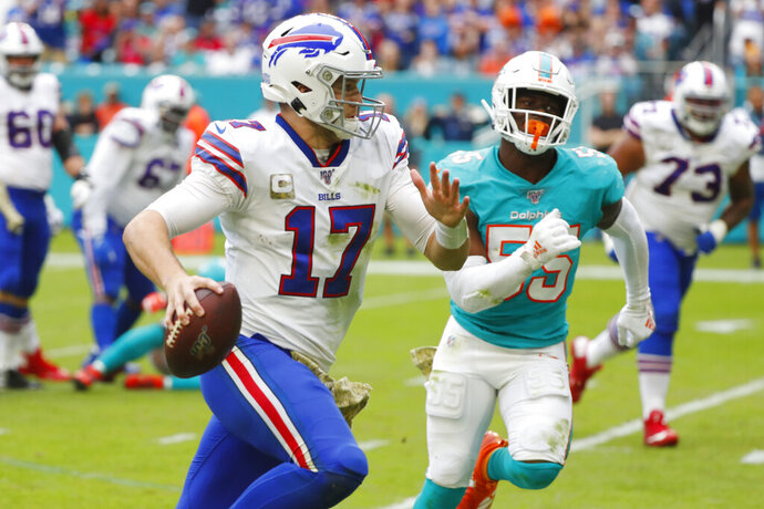 Buffalo Bills quarterback Josh Allen (17) runs for a touchdown ahead of Miami Dolphins outside linebacker Jerome Baker (55), during the second half at an NFL football game, Sunday, Nov. 17, 2019, in Miami Gardens, Fla. (AP Photo/Wilfredo Lee)