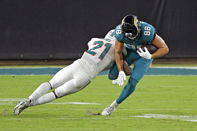 Miami Dolphins safety Eric Rowe (21) tackles Jacksonville Jaguars tight end Tyler Eifert (88) after a reception during the second half of an NFL football game, Thursday, Sept. 24, 2020, in Jacksonville, Fla. (AP Photo/Phelan M. Ebenhack)