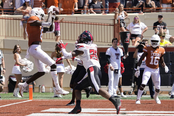 Texas wide receiver Xavier Worthy (8) catches a touchdown pass against Texas Tech defensive back Dadrion Taylor-Demerson (25) during the second half of an NCAA college football game on Saturday, Sept. 25, 2021, in Austin, Texas. (AP Photo/Chuck Burton)