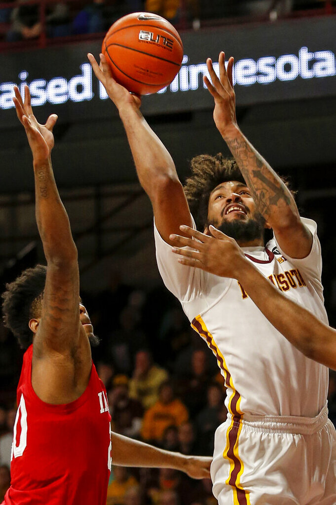 Minnesota's Jordan Murphy (3) shoots as he is fouled by Indiana's Juwan Morgan, right, as De'Ron Davis, left, helps to defend in the first half of an NCAA college basketball game Saturday, Feb. 16, 2019, in Minneapolis. (AP Photo/Bruce Kluckhohn)
