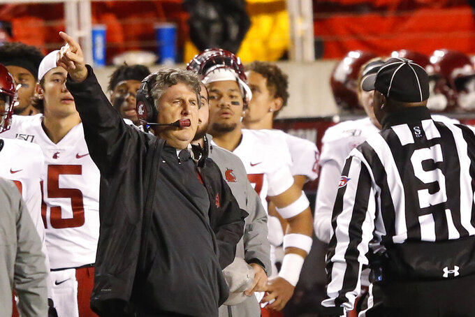 Washington State head coach Mike Leach speaks with a official in the first half of an NCAA college football game against Utah Saturday, Sept. 28, 2019, in Salt Lake City. (AP Photo/Rick Bowmer)