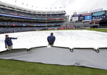 Members of the grounds crew pull the tarp off the field during a rain delay before a baseball game between the New York Yankees and the Baltimore Orioles at Yankee Stadium, Sunday, March 31, 2019, in New York. (AP Photo/Seth Wenig)