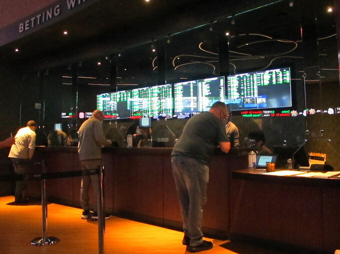 FILE - In this Friday, March 19, 2021, file photo, people line up to make sports bets at the Borgata casino in Atlantic City, N.J. On Wednesday, Oct. 20, 2021, the NFL announced it is spending $6.2 million on a responsible betting program with the National Council on Problem Gambling to teach people how to bet on sports responsibly and to fund and expand treatment and prevention programs for compulsive gambling. (AP Photo/Wayne Parry, File)