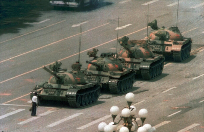 FILE - In this June 5, 1989, file photo, a Chinese man stands alone to block a line of tanks heading east on Beijing's Changan Boulevard in Tiananmen Square. The man, calling for an end to the recent violence and bloodshed against pro-democracy demonstrators, was pulled away by bystanders, and the tanks continued on their way. (AP Photo/Jeff Widener, File)