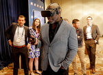 Los Angeles Chargers head coach Anthony Lynn wears a virtual reality mask to view the new Los Angeles Stadium at Hollywood Park during the annual NFL football owners meetings, Tuesday, March 26, 2019, in Phoenix. (AP Photo/Matt York)