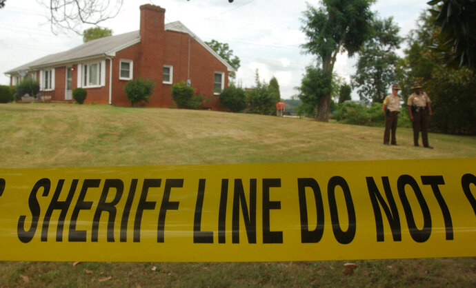 In this Aug. 16, 2002, file photo, police have taped off the area surrounding the Short residence in Bassett, Va., where authorities said they still had no suspects in the slayings or in the disappearance of Jennifer Renee Short, who vanished from the western Virginia home where her parents were shot to death. More than 16 years after the still-unsolved slayings of the Short family, their Virginia home has burned to the ground. The Martinsville Bulletin reports that the former home of Michael, Mary and Jennifer Short was destroyed by fire early Wednesday morning, Feb. 20, 2019. Collinsville Volunteer Fire Department Chief Tyler Beam says the house appeared unoccupied. (AP Photo/Frank Franklin II, File)