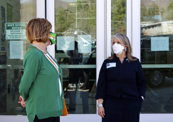 This photo provided by the Office of the Governor shows New Mexico Governor Michelle Lujan Grisham, right, is greeted by Aspen Elementary School Principal Michele Altherr, during a visit to Aspen Elementary School in Los Alamos on Monday, April 5, 2021. New Mexico's public schools are reopening for full-time, in-person learning this week. The shift to in-person learning is expected to relieve parent's year-long struggles with child care, unmet special needs, and spotty home internet.  (Nora Meyers Sackett/Office of the Governor via AP)
