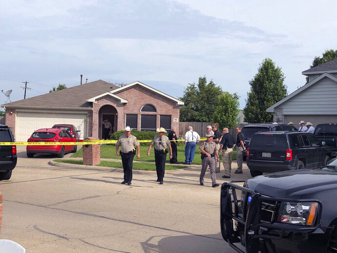 Denton County Sheriff Deputies work the scene of a shooting in Ponder, Texas where multiple people died Wednesday, May 16, according to Capt. Orlando Hinojosa, a spokesman for the Denton County Sheriff's Office.  (Julian Gill/The Denton Record-Chronicle via AP)