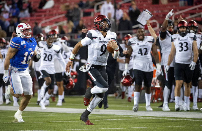 Cincinnati quarterback Desmond Ridder (9) breaks away from SMU linebacker Trevor Denbow (16) on a touchdown run during the second half of an NCAA college football game Saturday, Oct. 24, 2020, in Dallas. Cincinnati won 42-13 and Ridder finished with 179 yards rushing. (AP Photo/Jeffrey McWhorter)