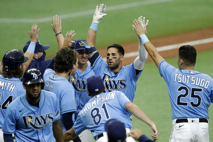 CORRECTS TO TRIPLE, INSTEAD OF DOUBLE - Tampa Bay Rays' Kevin Kiermaier, second from right, celebrates with teammates, including Yoshitomo Tsutsugo, of Japan, after his two-run walk-off triple off Toronto Blue Jays relief pitcher Shun Yamaguchi during the 10th inning of a baseball game Sunday, July 26, 2020, in St. Petersburg, Fla. (AP Photo/Chris O'Meara)