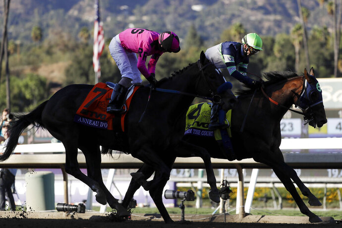 Storm the Court, right, with Flavien Prat, edges out Anneau D'or in the Breeders' Cup Juvenile horse race at Santa Anita, Friday, Nov. 1, 2019, in Arcadia, Calif. (AP Photo/Gregory Bull)
