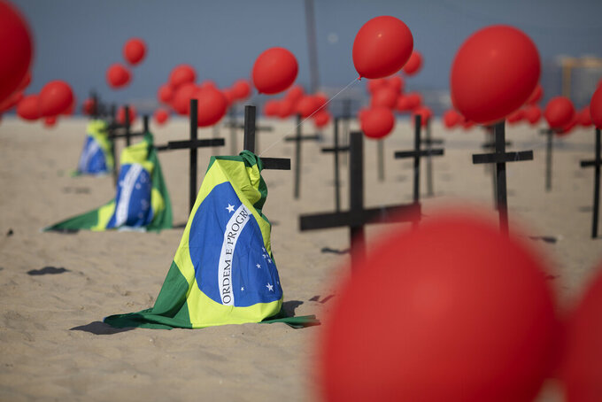Crosses, red balloons and Brazilian nation flags are placed in the sand on Copacabana beach in a demonstration organized by Rio de Paz to honor the victims of COVID-19, as the country heads to a milestone of 100,000 new coronavirus related deaths, in Rio de Janeiro, Brazil, Saturday, Aug. 8, 2020. (AP Photo/Silvia Izquierdo)