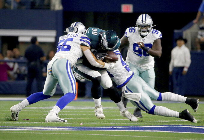 Dallas Cowboys' Leighton Vander Esch (55) and Jaylon Smith, right, tackle Philadelphia Eagles' Dallas Goedert (88) who fumbles the ball in the first half of an NFL football game in Arlington, Texas, Oct. 20, 2019. The Cowboys recovered the fumble. (AP Photo/Michael Ainsworth)