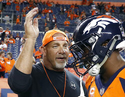 FILE - In this Sept. 11, 2017, file photo, professional wrestler Bill Goldberg, left, greets Denver Broncos outside linebacker Von Miller prior to an NFL football game against the Los Angeles Chargers in Denver. Bill Goldberg punched through the drywall in his garage one day this week -- not as some sort of masochistic training for his next WWE match --  but for repairs on property damage suffered as a result of the deadly Texas storms. The WWE Hall of Famer spent about 12 hours Wednesday, Feb. 24, 2021 replacing pumps in the wells on the ranch he owns just outside San Antonio, and then it was off to work on a garage and pool house that had been flooded. (AP Photo/Jack Dempsey, File)