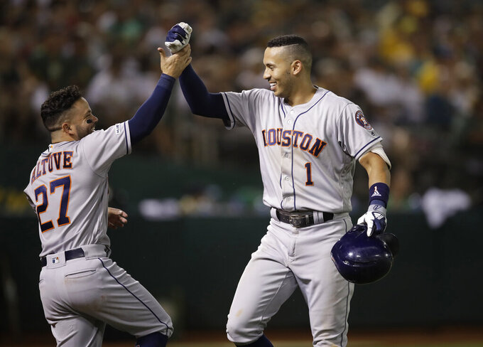 Houston Astros' Carlos Correa, right, celebrates with Jose Altuve (27) after hitting a home run against the Oakland Athletics during the seventh inning of a baseball game Thursday, Aug. 15, 2019, in Oakland, Calif. (AP Photo/Ben Margot)