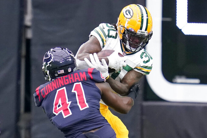 Green Bay Packers running back Jamaal Williams (30) runs for a short gain as Houston Texans linebacker Zach Cunningham (41) defends during the first half of an NFL football game Sunday, Oct. 25, 2020, in Houston. (AP Photo/Sam Craft)