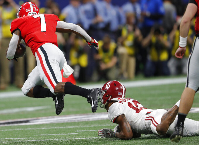 Georgia running back D'Andre Swift (7) his tripped up by Alabama defensive back Xavier McKinney (15) during the first half of the Southeastern Conference championship NCAA college football game, Saturday, Dec. 1, 2018, in Atlanta. (AP Photo/John Bazemore)