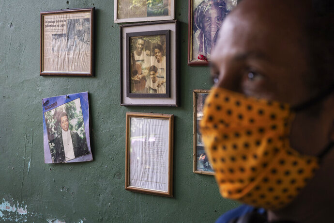 Marcio Antonio do Nascimento stands next to a framed childhood image of his 25-year-old son Hugo do Nascimento  who died from the new coronavirus, in Rio de Janeiro, Brazil, Saturday, Aug. 1, 2020. Brazil was leaping toward a grim milestone, 100,000 deaths from COVID-19, on Saturday, Aug. 8, and five months after the first reported case, the country had not shown signs of crushing the disease. (AP Photo/Leo Correa)