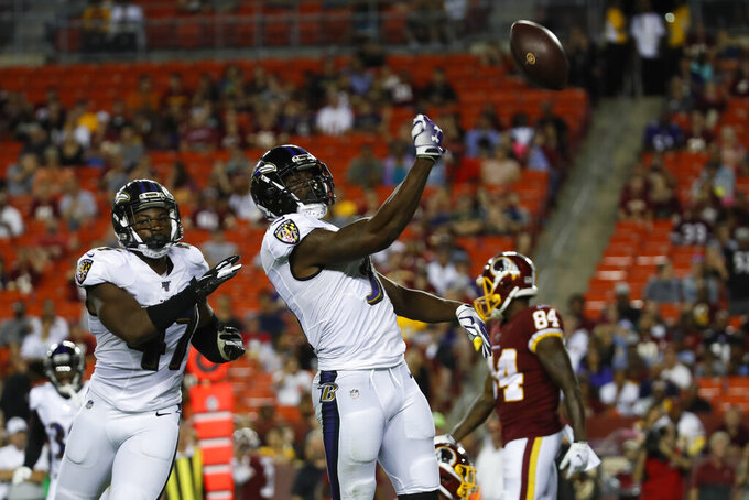 Baltimore Ravens defensive back Brynden Trawick, center, throws the ball after his interception as he celebrates with linebacker Donald Payne, left, during the second half of an NFL preseason football game against the Washington Redskins, Thursday, Aug. 29, 2019, in Landover, Md. (AP Photo/Alex Brandon)