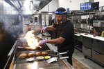 A cook prepares a meal at Slater's 50/50 Wednesday, July 1, 2020, in Santa Clarita, Calif. California Gov. Gavin Newsom has ordered a three-week closure of bars, indoor dining and indoor operations of several other types of businesses in various counties, including Los Angeles, as the state deals with increasing coronavirus cases and hospitalizations. (AP Photo/Marcio Jose Sanchez)