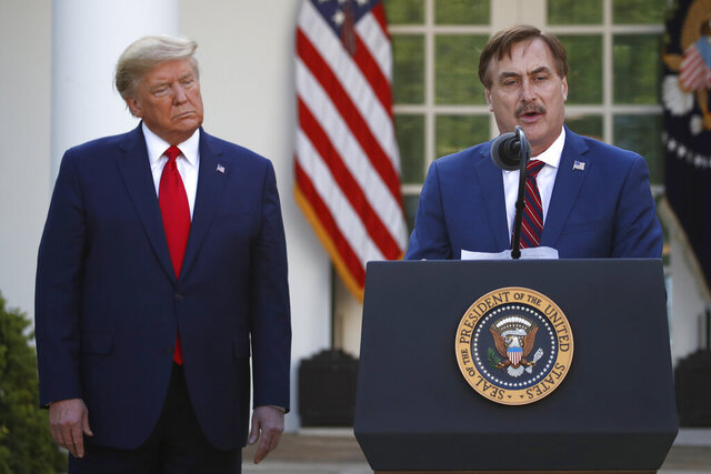 FILE - In this March 30, 2020 file photo, My Pillow CEO Mike Lindell speaks as President Donald Trump listens during a briefing about the coronavirus in the Rose Garden of the White House, in Washington. Lindell, an avid supporter of President Donald Trump, who has continued to push the notion of election fraud since Trump lost to Joe Biden in the presidential election in November, said his products will no longer be carried in the stores of some retailers, including Bed Bath & Beyond and Kohl's.  (AP Photo/Alex Brandon, File)