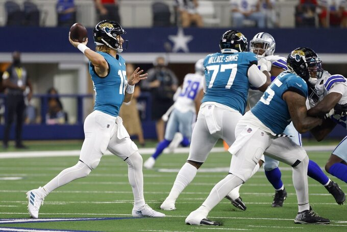 Jacksonville Jaguars quarterback Trevor Lawrence (16) throws a pass under protection from Jacksonville Jaguars' Tre'Vour Wallace-Simms (77) and Jawaan Taylor, right, in the first half of a preseason NFL football game against the Dallas Cowboys in Arlington, Texas, Sunday, Aug. 29, 2021. (AP Photo/Ron Jenkins)