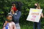 FILE - In this June 2, 2020, file photo, Ericka Ward-Audena, of Washington, stands with her daughter Elle Ward-Audena, 7, during a protest of President Donald Trump's visit to the Saint John Paul II National Shrine, in Washington.