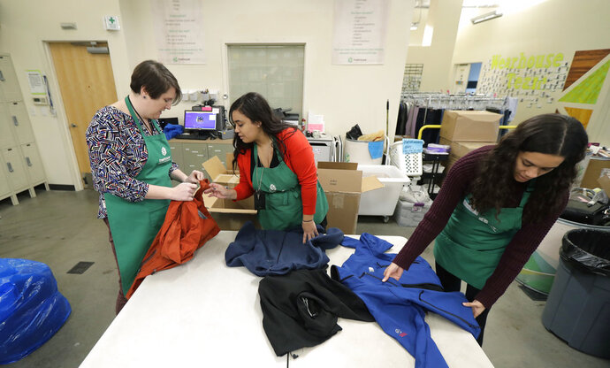 In this Friday, Dec. 21, 2018, photo, from left, Rebecca Schaechter, Nicole Herron and Rachel Herron fold and sort donated clothes at Treehouse, a nonprofit organization in Seattle that serves the needs of children in the foster-care system. The charity was one of several that received donations from the $11 million secret estate of Alan Naiman -- a social worker who died from cancer earlier in 2018 after living a private life of frugality and concern for children facing hardship. (AP Photo/Ted S. Warren)