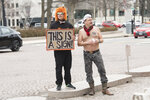 Local D.C. artist Mike Green, left, looks on as Adam Eidinger, with Radical Matriarchy, protests topless outside the National Gallery of Art on Thursday, Feb. 14, 2019 in Washington. Radical Matriarchy was protesting the fact that 90% of the art inside is by white men. In the nation's capital, it can be hard for protesters to stand out. Fifty people _ or even 500 _ holding signs and shouting hardly merits a second glance in this city of protests. That's why Washington activists have to get creative. (AP Photo/Kevin Wolf)