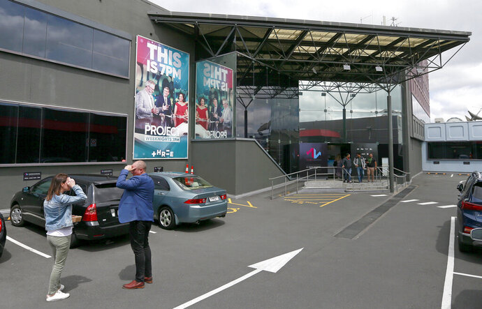 People stand outside the MediaWorks building at Flowers St in Auckland, New Zealand, Friday, Oct. 18, 2019. New Zealand broadcaster MediaWorks has announced it plans to sell its struggling television business, leaving hundreds of workers wondering if they will still have jobs if a buyer can't be found. The move also raises the possibility the country could be left with a single state-owned broadcaster to report most television news. (Alex Burton/New Zealand Herald via AP)