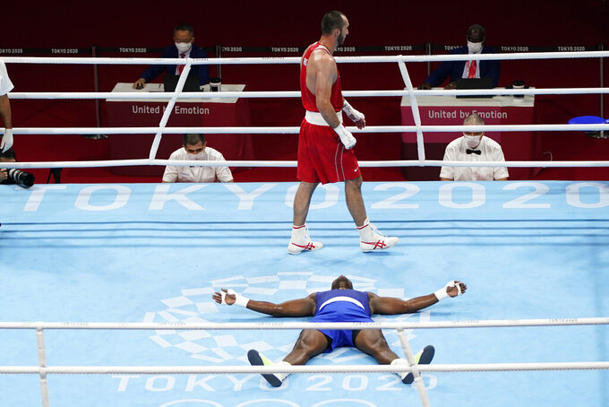Muslim Gadzhimagomedov, of the Russian Olympic Committee, top, walks past Cuba's Julio la Cruz as he lays on the mat in celebration after their men's heavyweight 91-kg boxing match at the 2020 Summer Olympics, Friday, Aug. 6, 2021, in Tokyo, Japan. (AP Photo/Frank Franklin II)