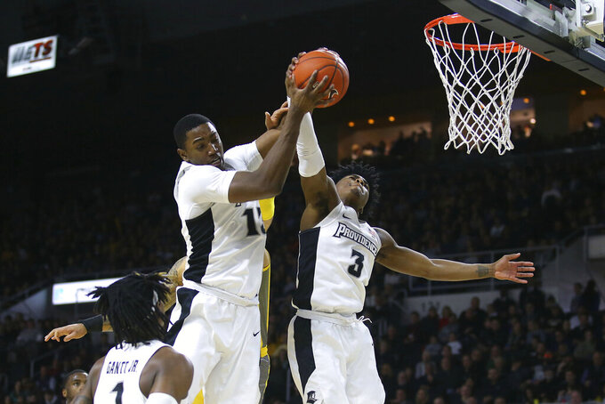 Providence's Kalif Young (13) and David Duke (3) battle for a rebound during the first half of an NCAA college basketball game against Marquette Saturday, Feb. 22, 2020, in Providence, R.I. (AP Photo/Stew Milne)