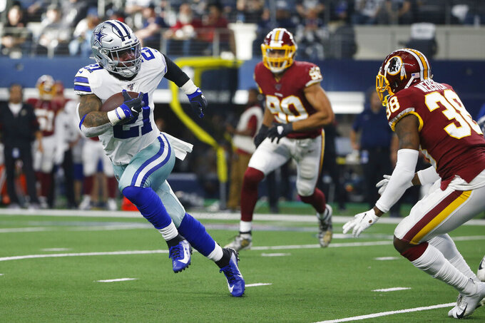 Dallas Cowboys running back Ezekiel Elliott (21) runs around Washington Redskins defensive back Kayvon Webster (38) during the first half of an NFL football game in Arlington, Texas, Sunday, Dec. 15, 2019. (AP Photo/Ron Jenkins)