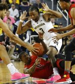 Michigan forward Isaiah Livers, left, steals the ball away from Maryland guard Darryl Morsell (11) during the first half of an NCAA college basketball game, Saturday, Feb. 16, 2019, in Ann Arbor, Mich. (AP Photo/Carlos Osorio)