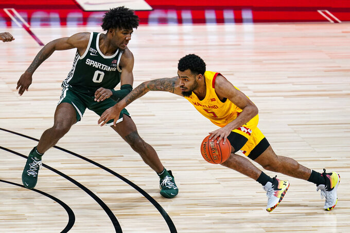 Maryland guard Eric Ayala (5) drives on Michigan State forward Aaron Henry (0) in the second half of an NCAA college basketball game at the Big Ten Conference tournament in Indianapolis, Thursday, March 11, 2021. Maryland defeated Michigan State 68-57. (AP Photo/Michael Conroy)