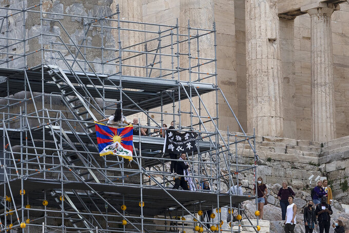 Protesters raise a Tibetan flag and a banner from scaffolding at the Acropolis hill, in Athens, Greece, Sunday, Oct. 17, 2021. Three people attempted to hang a banner from the Acropolis in Athens Sunday morning in protest at the upcoming Beijing Winter Olympics but were arrested before completing their mission. (AP Photo/Yorgos Karahalis)