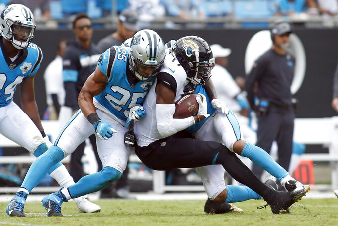 Carolina Panthers strong safety Eric Reid (25) tackles Jacksonville Jaguars wide receiver D.J. Chark (17) during the second half of an NFL football game in Charlotte, N.C., Sunday, Oct. 6, 2019. (AP Photo/Brian Blanco)