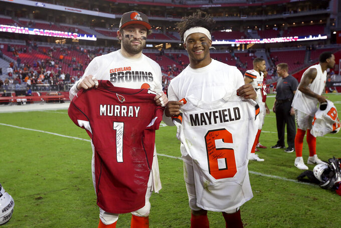 FILE- In this Dec. 15, 2019, file photo, Arizona Cardinals quarterback Kyler Murray, right, and Cleveland Browns quarterback Baker Mayfield exchange jerseys after an NFL football game in Glendale, Ariz. Back-to-back Heisman Trophies at Oklahoma followed, then No. 1 overall draft picks and now NFL fame as starting quarterbacks, Murray and Mayfield are forever linked. On Sunday, their close friendship gets put on hold. (AP Photo/Ross D. Franklin, File)